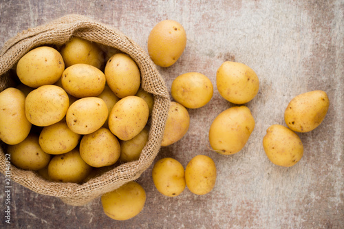 Foto Murales Sack of fresh raw potatoes on wooden background, top view.