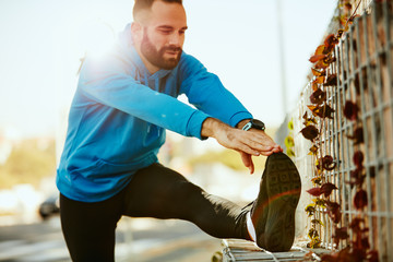 Young bearded male runner stretching legs before running. Wearing sportswear, healthy lifestyle concept.