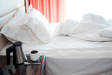 Hotel room in morning, bed after sleep, Kettle and Cup on the bedside table - 231154107
