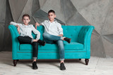 Portrait of two brothers. Guys are sitting on couch - 231156956