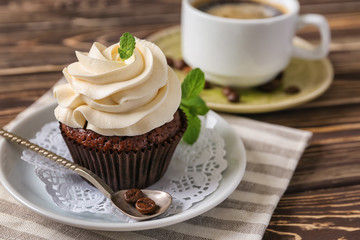 Tasty chocolate cupcake on wooden table