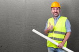 construction worker holding blueprint against a grey wall - 231165111