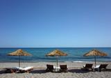Loungers under palm tree leaves parasols on beach on Samos island, Greece - 231167388