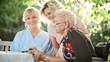 Seniorin beim Kreuzworträtzeln mit Tochter und Pflegerin - 231178909