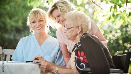 Seniorin beim Kreuzworträtzeln mit Tochter und Pflegerin © Karin & Uwe Annas