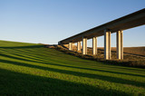 Bridge, modern transport and infrastructure building. Landscape and countryside with meadow around architecture. Yellow sunset and sundown light in the evening. Shadows as stripes on the grass