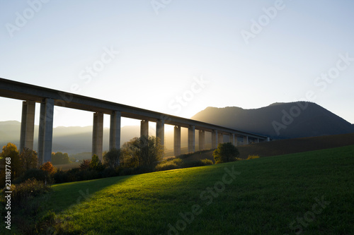 Bridge, modern transport and infrastructure building. Beautiful landscape and countryside with hills, mountains and meadow around architecture. Backlight sun in the evening during sunset and sundown - 231187768