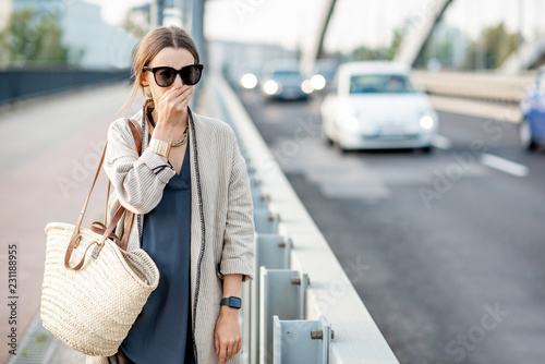 fototapeta na ścianę Woman closing her nose feeling bad because of the air pollution on the bridge with traffic in the city