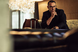 Businessman waiting at hotel lobby looking at camera - 231190126