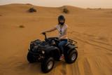 desert Quad Biking. Young girl in helmet driving a Quad bike - 231190180