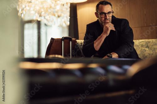 Foto Murales Businessman waiting at hotel lobby looking at camera