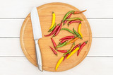 Cutting board with small chilli colorful peppers and knife on white wooden background. Top view.