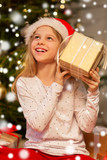 christmas, holidays and childhood concept - smiling girl in santa helper hat with gift box at home - 231197120