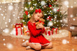 christmas, holidays and childhood concept - girl in red dress hugging teddy bear at home