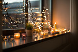 hygge, decoration and christmas concept - candles burning in lanterns on window sill and festive garland string at home - 231201162