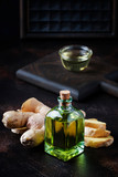 Ginger oil and fresh ginger root, dark table, selective focus - 231201183