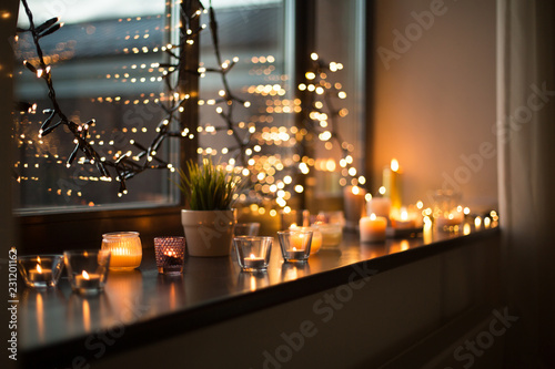 Leinwanddruck Bild hygge, decoration and christmas concept - candles burning in lanterns on window sill and festive garland string at home