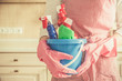 Cleaning concept - female holding cleaning supplies in blue basket, copy space, kitchen background
