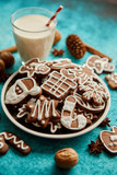 Sweet Christmas composition. Assortment of gingerbread cookies on a plate. Glass of milk, vanilla sticks, anise, pine, walnut. Top view. On blue background. - 231213145