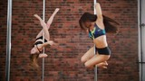 Two women practicing in a pole fitness class on the background of brick wall. Dynamic pylon. Slow motion - 231224757