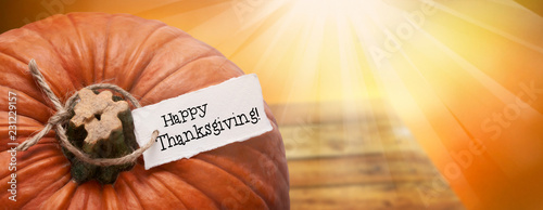 Leinwanddruck Bild Happy Thanksgiving message on a tag tied to a large orange pumpkin with a bright sunshine background.