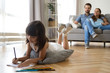 Leinwandbild Motiv Diverse family in living room at home. Focus on little preschool adorable concentrated daughter lying at soft cushion on warm wooden floor young parents married couple sitting on sofa looking at kid