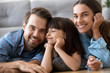 Leinwandbild Motiv Close up little cute daughter holding hands on chin with closed eyes lying on warm floor with parents in living room at home married couple smiling and looking at camera. Happy diverse family concept