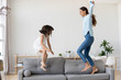 Leinwandbild Motiv Full length positive mother and little daughter having fun jumping together on sofa in living room at home. Adorable girl playing enjoying active weekends with elder sister nanny or loving mom indoors