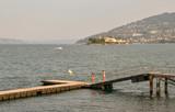 Pontile sul lago con isole e costa sullo sfondo al tramonto, Stresa, Isola dei Pescatori, Isola Bella, Lago Maggiore, Italia - 231237107