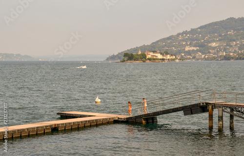 Acrylglas Pier Pontile sul lago con isole e costa sullo sfondo al tramonto, Stresa, Isola dei Pescatori, Isola Bella, Lago Maggiore, Italia