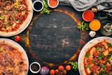 A set of Italian pizza. Italian cuisine. On a black wooden background. Free copy space. Top view. - 231239557