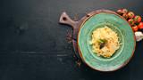 Pasta with Parmesan in the green plate. Italian cuisine. On the old background. Free copy space. Top view.