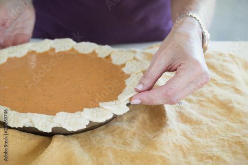 Wall mural Close up photograph of a woman's hands making the crust of a pumpkin pie