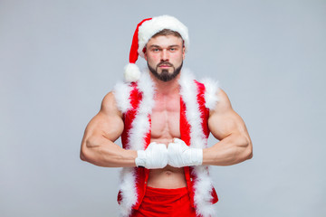 Christmas. Sexy Santa Claus . Young muscular man wearing Santa C © satyrenko