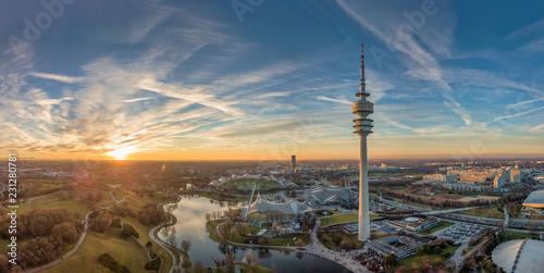 canvas print picture Der Olympiapark in München als Luftaufnahme einer Drohne zum Sonnenuntergang im Herzen von München