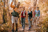 Man holding map and showing other hikers right way while walking in woods. - 231302385