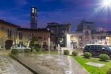 City of north Italy at dusk. Somma Lombardo, province of Varese, picturesque view of one of the areas of the historic center, Square Scipione with the bell tower of the church of S. Agnese - 231314550