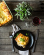 Piece of tasty hot lasagna with red wine. Small depth of field. Traditional italian lasagna. Portion. Italian food. Food on black plate. Bolognese sauce. Bechamel sauce. Still life of food.