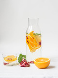 Water with orange slices, pomegranate seeds and mint in a glass jug on a white background