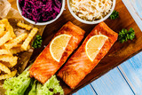 Grilled salmon with french fries and vegetables served on cutting board on wooden table - 231346169