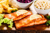 Grilled salmon with french fries and vegetables served on cutting board on wooden table - 231346350