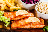 Grilled salmon with french fries and vegetables served on cutting board on wooden table - 231346398