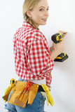 Woman drilling in wall - 231374381