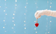 Hand holding a heart ornament on a shiny light blue background