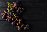 Top view of fresh ripe black grapes on dark wooden table with copy space.