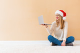 Young woman with santa hat using her laptop on a white carpet