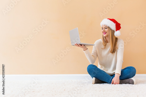 Leinwanddruck Bild Young woman with santa hat using her laptop on a white carpet