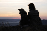 Woman with a dog meets the dawn on the top of the mountain. - 231387550