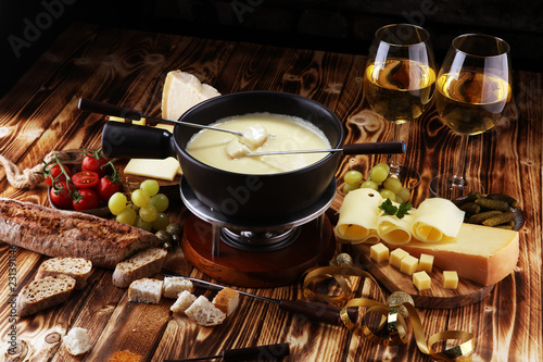 Leinwanddruck Bild Gourmet Swiss fondue dinner on a winter evening with assorted cheese