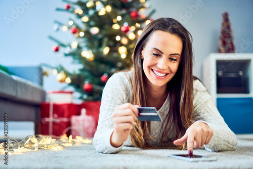 Leinwanddruck Bild Photo of woman paying for christmas shopping with credit card online